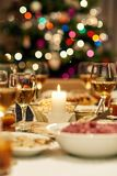 Close up of Christmas dinner feast table. Warm mood around dining table full of a variety of delicious festive food and wine with a Christmas tree in the Royalty Free Stock Images