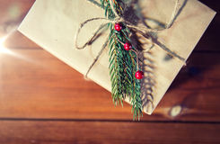 Close up of christmas gift box with fir brunch. Christmas, holidays, presents, new year and decor concept - close up of gift box wrapped into brown mail paper Royalty Free Stock Photography