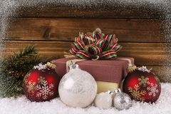 Close up on a Christmas gift box with ribbon and bow. Snow, bauble and branch in decoration. royalty free stock images