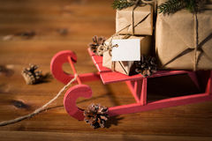 Close up of christmas gifts with note on sleigh Stock Photography