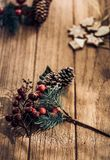 Close up of Christmas mistletoe leaf and pine cone on wood plank table with sunlight through window stock photography