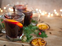 Close-up of Christmas mulled wine on wooden background. Close-up of Christmas mulled wine with oranges, star anise, cloves and cinnamon sticks in clear glasses stock photography