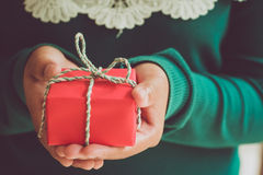 Close-up Christmas and New Year presents. Girl hands holding Christmas red gift box, handmade and craft. vintage styles royalty free stock image