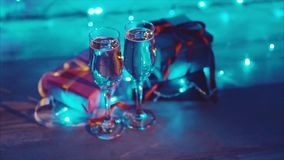 Close up christmas presents and two glasses of bubbling champagne blue bokeh stock footage