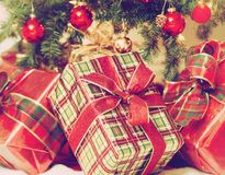 Close-up of Christmas presents under the tree. Christmas presents under the tree. Close-up. Christmas tree with ornaments in the background. Vintage filter royalty free stock photos