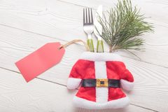 Close-up of Christmas Santa costume with fork, knife, green fir decor royalty free stock photos