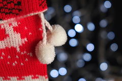 Close-up of Christmas stocking hanging with Christmas lights behind Stock Images