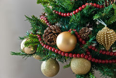 Close-up of Christmas tree. Close-up of decorated Christmas tree with cone, yellow ornaments and red berries Stock Images