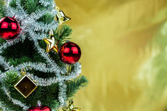 Close-up of christmas tree decorated with ornaments in rich shiny gold background - with copyspace Royalty Free Stock Photos