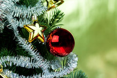 Close-up of christmas tree decorated with ornaments in rich shiny gold background - with copyspace Royalty Free Stock Images