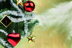 Close-up of christmas tree decorated with ornaments in rich shiny gold background - with copyspace Stock Images