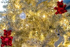 Close up Christmas tree decoration with white balls, silver reindeer and red bear and golden light. Xmas background. Christmas. And Happy New Year background stock image