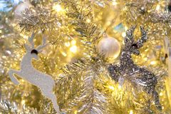 Close up Christmas tree decoration with white balls, silver reindeer and red bear and golden light. Xmas background. Christmas. And Happy New Year background stock photo