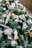 Close up of Christmas tree with ornaments baubles, bow, snowflakes, pine cones and lights. Stock Images