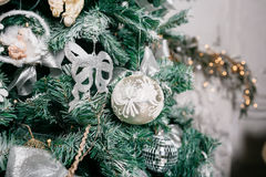 Close up of Christmas tree with ornaments baubles, bow, snowflakes, pine cones and lights. Stock Photo