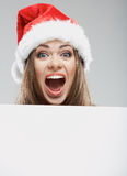 Close up christmas woman portrait behind big white card. Emotio Stock Photography