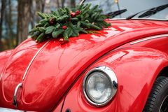 Close up Christmas wreath on red retro car. Close-up red retro car outdoors with Christmas wreath on top of it, festive composition background royalty free stock photo