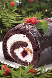 Close up of Christmas yule log cake on plate under tree Royalty Free Stock Image
