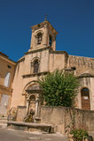Close-up of church with steeple and flowers, in Lourmarin. Close-up of church with steeple and flowers, in the historical village of Lourmarin. Located in the Stock Image