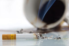 Close up of cigarette and coffee spill. Stock Photos