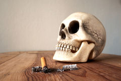 Close up of cigarette stub and blured  human skull Stock Image