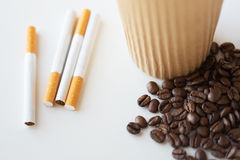 Close up of cigarettes, coffee cup and beans Stock Photo