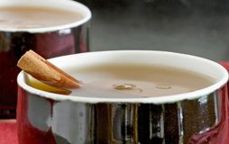 Close-up cinnamon tea. Close-up macro steaming steam tea in a black exterior and a white interior antique oriental teacup sitting on a burgundy tabletop place Stock Images
