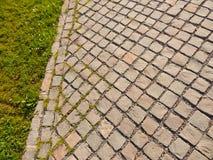 Close-up cinzento da estrada da pedra com grama verde Fotografia de Stock Royalty Free