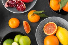 Close up of citrus in bowls fruits on stone table royalty free stock image