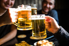 Close up of clanging glasses of beer of three friends in pub. Three young men are smiling and clanging glasses of beer together while sitting in pub royalty free stock images