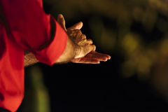 Close up of the clasped hands of a male flamenco dancer. Wearing a red shirt in the darkness which could indicate clapping, anxiety or washing them, view from Stock Photos