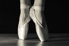 Close-up classic ballerina`s legs in pointes on the black background and wooden grey floor. Stock Photo