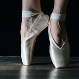 Close-up classic ballerina's legs in pointes on the black background and wooden grey floor. Close-up classic ballerina's legs in pointes on the Royalty Free Stock Photography