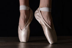 Close-up classic ballerina's legs in pointes on the black background and wooden grey floor. Close-up classic ballerina's legs in pointes on the black background Stock Photo