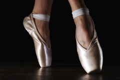 Close-up classic ballerina`s legs in pointes on the black floor Stock Images