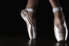 Close-up classic ballerina`s legs in pointes on the black floor Stock Image