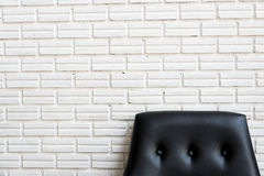Close up classic black sofa and white brick wall Royalty Free Stock Images