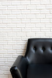 Close up classic black sofa and white brick wall Royalty Free Stock Photos