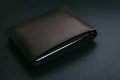 Close Up Classic dark brown leather wallet. On black leather background Stock Image