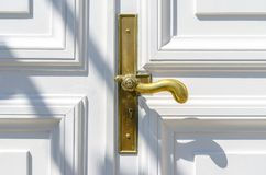 Close up of classic golden door handle on white door stock image