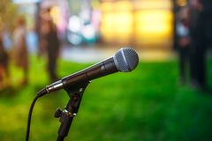 Close up classic microphone on Abstract blurred bright green background of conference hall or event. Public speaking concept. Selective focus. copy space royalty free stock photography