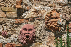 Close-up of clay masks attached to the wall in Colle di Val d`Elsa. A graceful village with its historic center preserved and known by its crystal production Stock Photography
