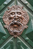 Close-up. Clclose-up of men headed door knocker on green painted wooden doorose-up of lion headed door knocker on green painted wooden door Royalty Free Stock Photography