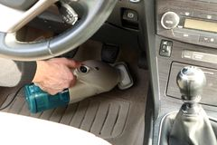 Close-up - cleaning in the car. Work with a vacuum cleaner. Close-up - cleaning in the car. Working with a vacuum cleaner and cleaning the green cloth inside the stock image
