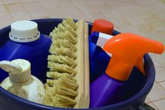 Cleaning items. Close up of cleaning items in blue plastic bucket on dirty bathroom floor stock photos