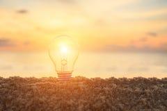 Clear light bulb on sunset beach, energy concept. Close up clear light bulb on sunset beach, energy concept Stock Photos