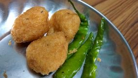 Fried Pakora. Close up click of Indian tasty and salty snack pakora seasoned with fried chillies royalty free stock images