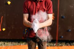Close up of climber man coating hands in powder chalk magnesium and preparing to climb outdoor training rock wall.  Royalty Free Stock Images