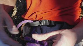 Close-up of climber in safety harness untie an eight knot