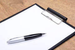 Close up of clipboard and pen on wooden table Stock Photos